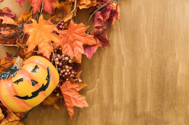 Halloween composition with autumn leaves and pumpkin