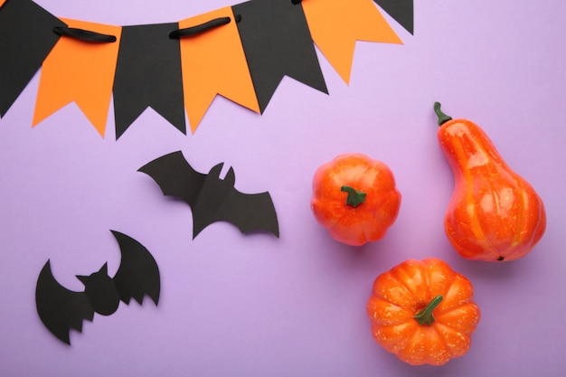 Halloween composition with bats and pumpkins on purple background. view from above. top view