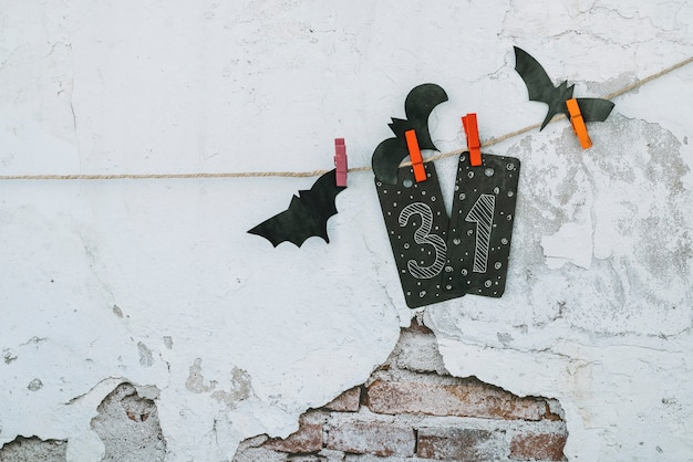 Halloween composition with carved bats hanging on rope
