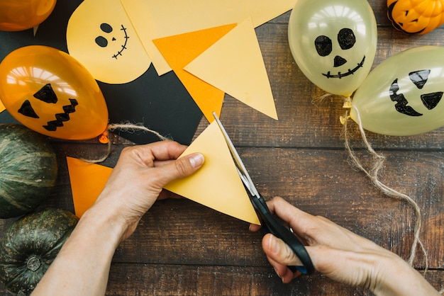 Halloween composition with hands cutting paper