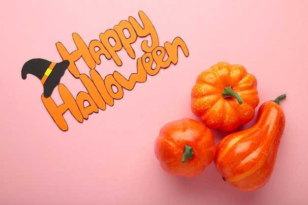 Halloween composition with pumpkins on pink background. view from above.