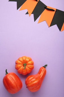 Halloween composition with pumpkins on purple background. view from above. vertical photo