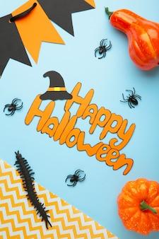Состав хеллоуина с пауками и тыквами на голубой предпосылке. вид сверху. вертикальное фото.