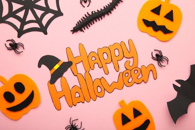 Состав хеллоуина с пауками и тыквами на розовом фоне. вид сверху. вертикальное фото.