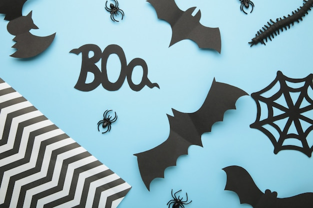 Halloween composition with spiders and bats on blue background. view from above.