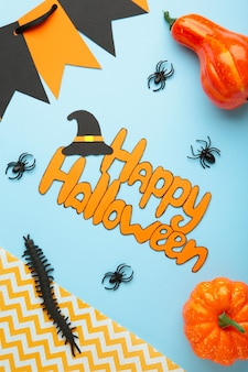 Halloween composition with spiders and pumpkins on blue background. top view. vertical photo.