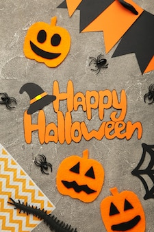 Halloween composition with spiders and pumpkins on grey background. view from above.