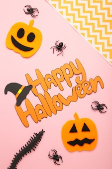 Halloween composition with spiders and pumpkins on pink background. top view. vertical photo.
