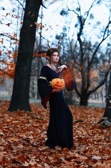 Концепция хэллоуина. ведьма в осеннем лесу с тыквой