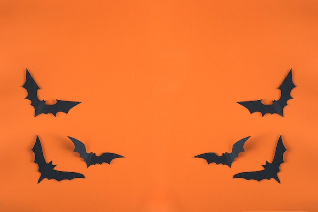 할로윈 컨셉과 종이 장식. 오렌지 배경에 검은 종이에서 잘라 박쥐. 종이 컷 스타일. 상위 뷰 복사 공간