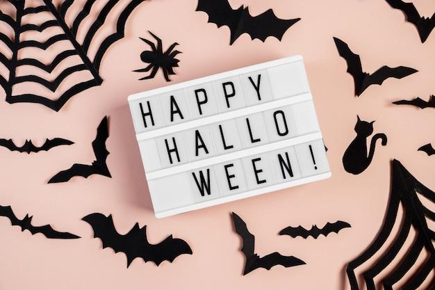Концепция хэллоуина. летучие мыши и пауки на розовом фоне. праздничные украшения.