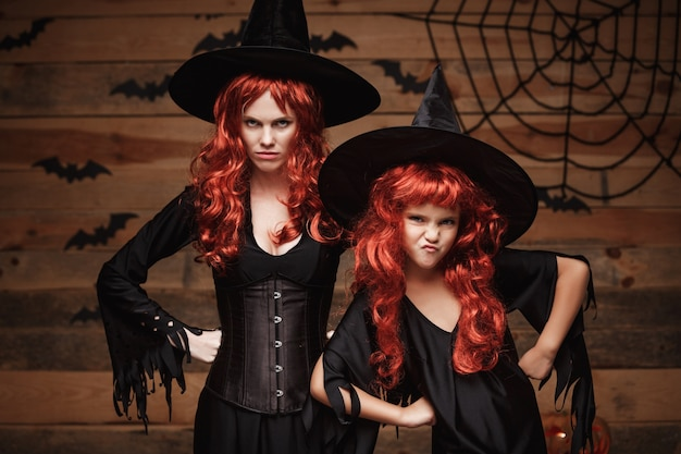 Halloween concept - beautiful caucasian mother and her daughter with long red hair in witch costumes with angry fussy facial expression.