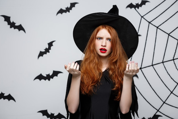 Concetto di halloween - bella strega caucasica scioccante con qualcosa sul muro grigio.
