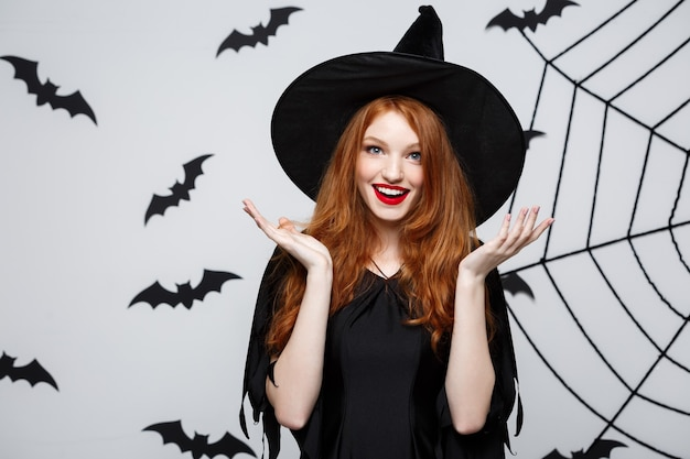 Halloween concept - beautiful caucasian witch surprising with something over grey wall.