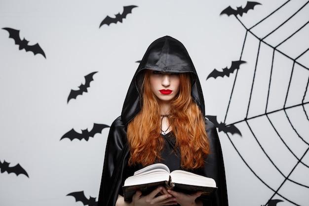 Concetto di halloween - bello incantesimo di colata del sacerdote scuro con il libro magico sulla parete grigia.