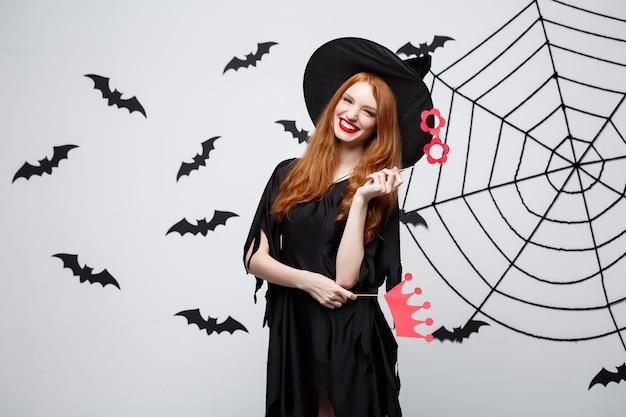 Concetto di halloween - belle ragazze in abiti neri da strega che tengono oggetti di scena per feste.