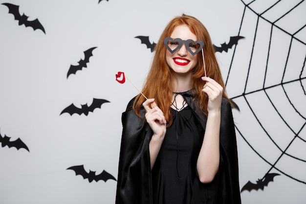 ハロウィーンのコンセプト-パーティーの小道具を保持している黒い魔女のドレスの美しい女の子。