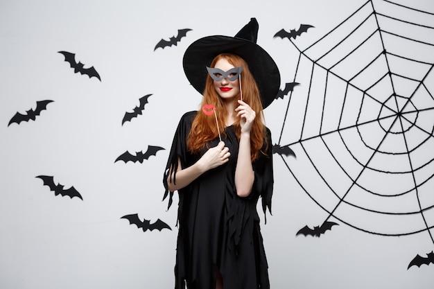 할로윈 컨셉 - 파티 소품을 들고 검은 마녀 드레스를 입은 아름다운 소녀들.