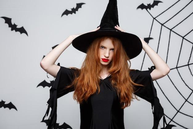 Concetto di halloween - bella strega seria con espressione facciale arrabbiata sul muro grigio.