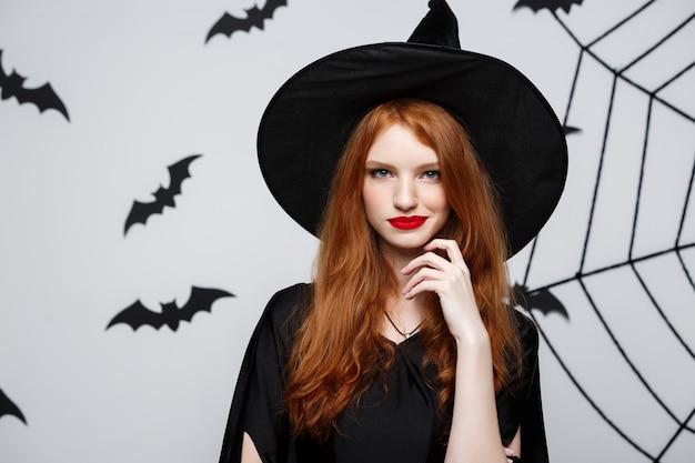 할로윈 개념 - 아름다운 마녀가 손을 잡고 회색 벽 너머로 웃고 있습니다.
