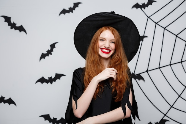 Halloween concept - beautiful witch holding hand and smiling over grey wall.