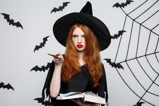 ハロウィーンのコンセプト-灰色の壁に魔法の棒で遊ぶ美しい魔女。