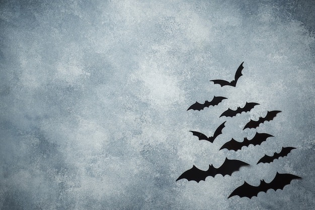 Halloween concept. black paper bats on grey