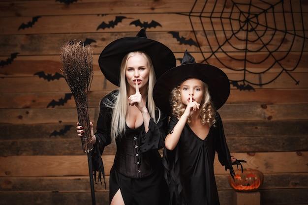 Концепция хэллоуина - веселая мать и ее дочь в костюмах ведьмы празднуют хэллоуин, делая жест молчания, позирующий с изогнутыми тыквами над летучими мышами и паутиной на фоне деревянной студии.