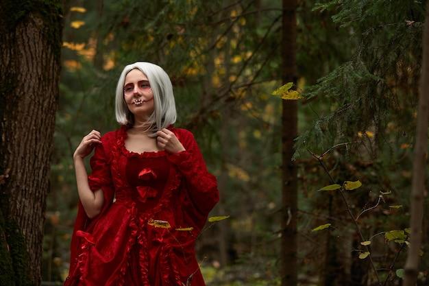 할로윈 컨셉, 화려한 의상 디테일. 하얀 드레스와 빨간 망토를 입은 숲 속의 젊고 아름답고 신비한 여자. 작은 빨간 후드 또는 뱀파이어 이야기.