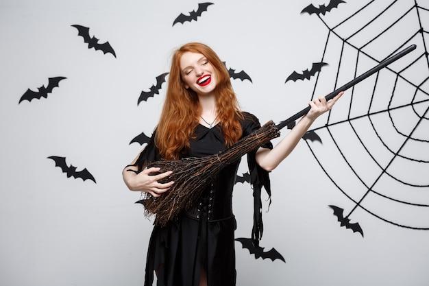 La strega felice ed elegante felice di concetto di halloween si diverte a giocare con la festa di halloween del manico di scopa sopra la parete grigia