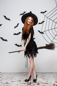 ハロウィーンのコンセプト幸せでエレガントな魔女は灰色の壁を越えてほうきのハロウィーンパーティーで遊ぶことをお楽しみください