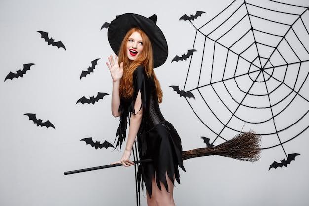할로윈 컨셉의 행복한 우아한 마녀는 회색 벽 위에서 빗자루 할로윈 파티를 가지고 노는 것을 즐깁니다.