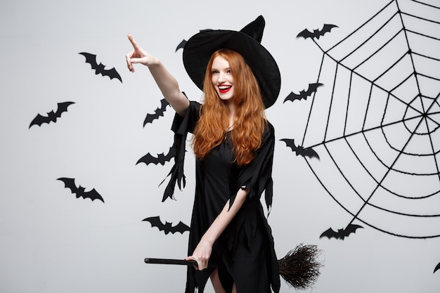 ハロウィーンのコンセプト幸せなエレガントな魔女はほうきで遊ぶことをお楽しみください