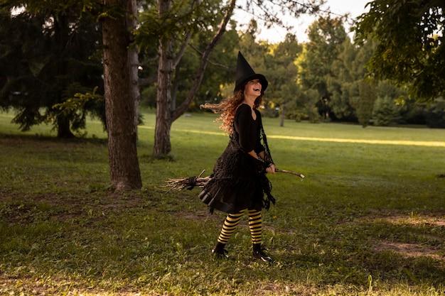 Концепция хэллоуина. маленькая кудрявая девушка в костюме ведьмы и черной длинной шляпе с деревянной метлой стоит на открытом воздухе на фоне осеннего леса, полного опавших листьев