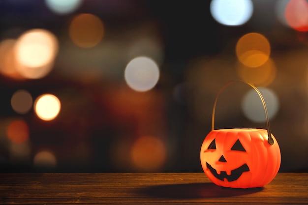 ハロウィーンのコンセプト – 暗い木のテーブルにオレンジ色のプラスチック製のカボチャ ランタン、背景にぼやけた輝く光、トリック オア トリート、クローズ アップ