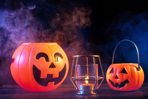 Halloween concept orange pumpkin lantern on a dark wooden table with double colored smoke