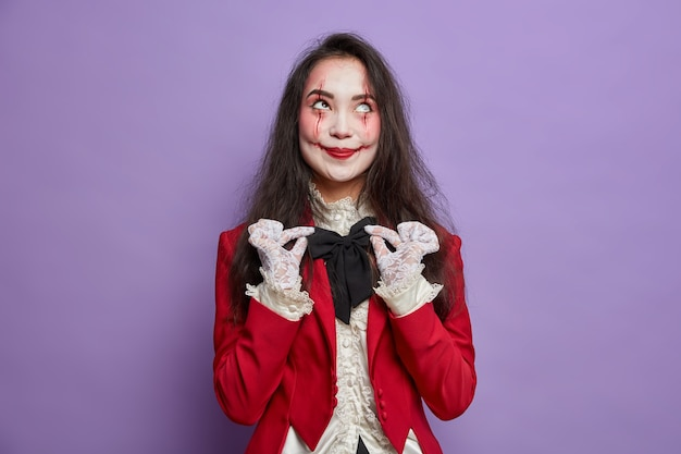 Halloween concept. pleased woman with spooky makeup wants to look scarying adjustes bowtie wears costume and has scars poses against purple wall. mystical character