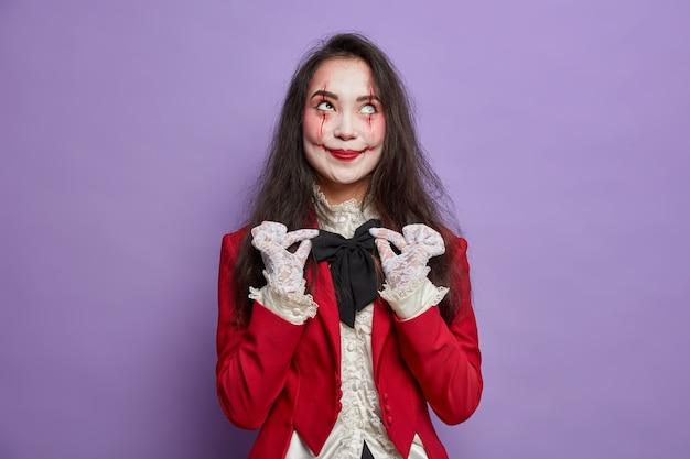 Концепция хэллоуина. довольная женщина с жутким макияжем хочет выглядеть устрашающе, поправляет костюм с бабочкой и позирует на фоне фиолетовой стены. мистический персонаж