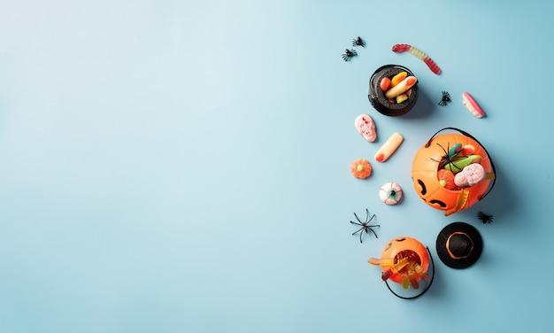 ハロウィーンのコンセプト。青い固体背景のカボチャ鍋で様々なハロウィーンのお菓子