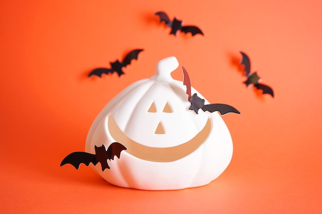 Концепция хэллоуина. белая тыква хэллоуина и летучие мыши на оранжевом фоне.