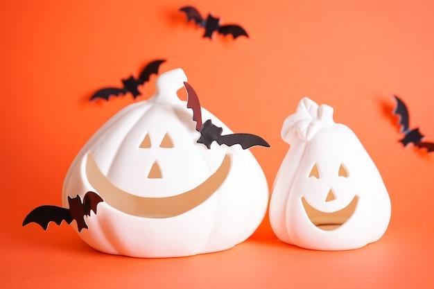 Концепция хэллоуина. белые тыквы хэллоуина и летучие мыши на оранжевом фоне.