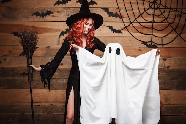 Concetto di halloween - strega madre e piccolo fantasma bianco che fanno dolcetto o scherzetto celebrando halloween in posa con zucche curve su pipistrelli e ragnatela su sfondo di studio in legno.