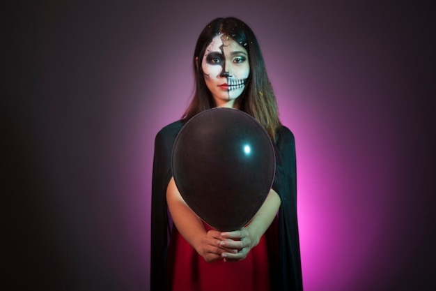 Halloween concept with girl holding balloon