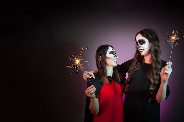 Halloween concept with women holding sparklers