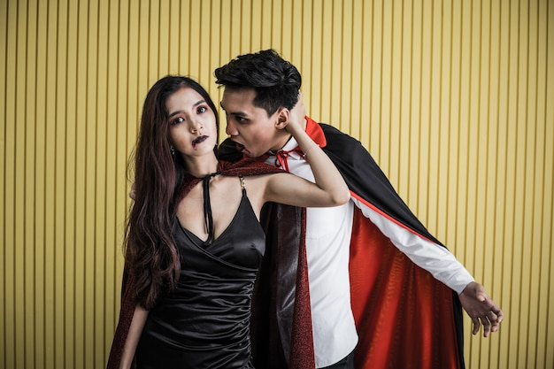 Halloween concept of young asian woman in costume witch and asian man in costume dracula on yellow background. portrait teen couple dressed up as witches and dracula for celebrate  halloween festival.