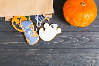 Halloween cookie in paper packet and pumpkin on desk