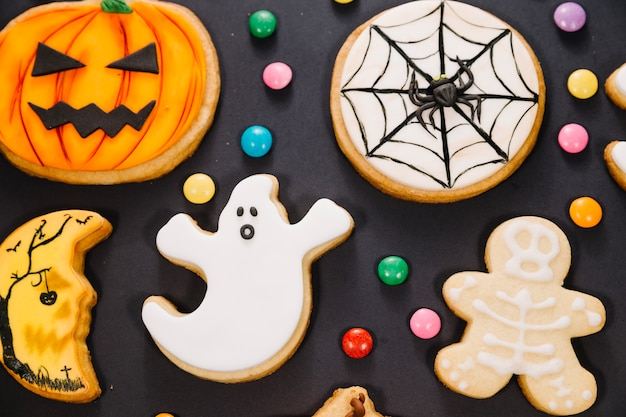 Halloween cookies among candy on black background