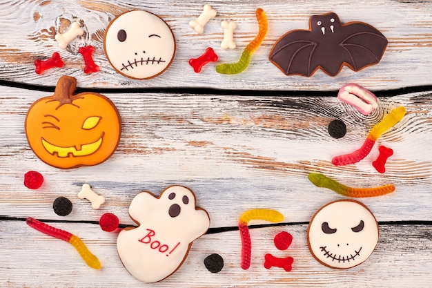 Halloween cookies and candies on wooden background.