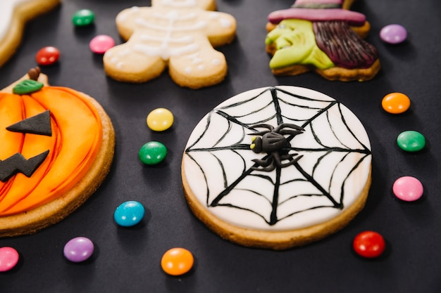 Halloween cookies and candy on black background