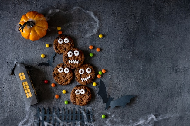 Halloween cookies. funny monsters made of biscuits with chocolate on the table. halloween party decoration. trick or treat concept.
